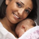 Young Attractive Ethnic Woman Holding Her Newborn